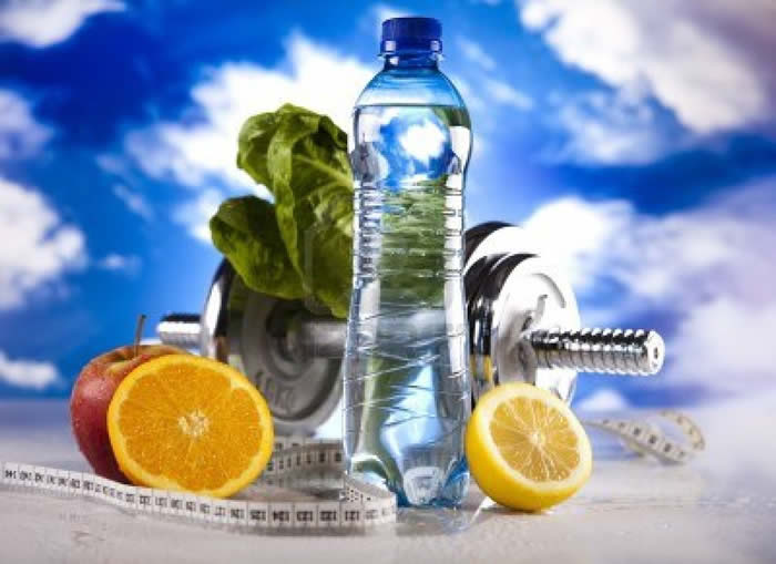 a Photo of a bottle of water, a chrome dumbbell and sliced fruit, with a blue sky background