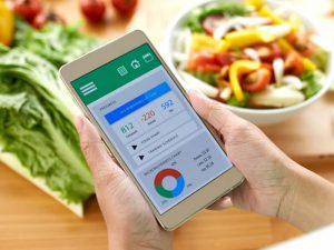 Photo of a calorie counting app on a mobile phone with some food in the background