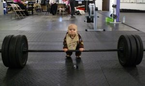 Photo showing a baby lifting weights